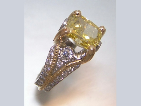 Center diamond is a 2.72 carat cushion cut fancy yellow Antwerp diamond.